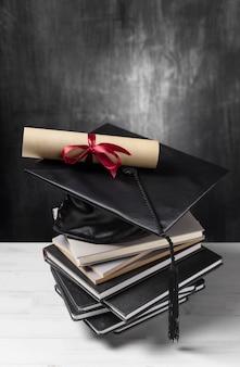 Pila de libros con diploma de graduación