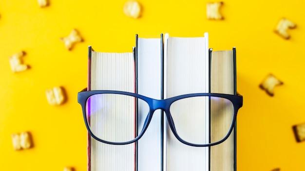 Una pila de libros con gafas es una imagen del rostro de una persona.