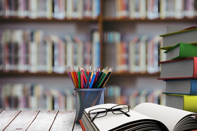 Pila de libros con gafas en escritorio de madera