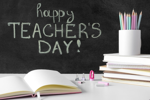Pila de libros y lápices feliz día del maestro concepto