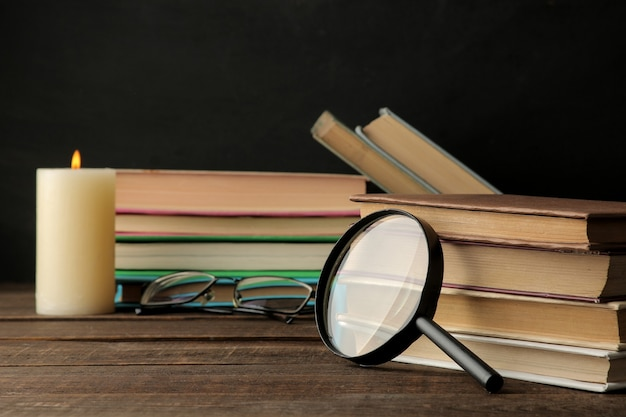 Una pila de libros y una lupa sobre una mesa de madera marrón y sobre un fondo negro. libros viejos. educación. colegio. estudio