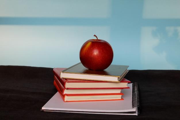 Pila de libros y manzana en la parte superior sobre fondo azul.