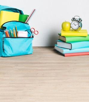 Pila de libros y mochila escolar en piso