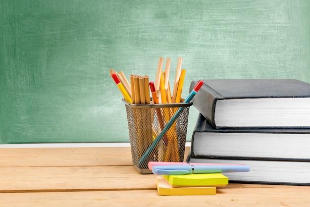 Pila de libros con papel de notas y bolígrafo con lápices en el contenedor de la cesta en la mesa de madera con pizarra
