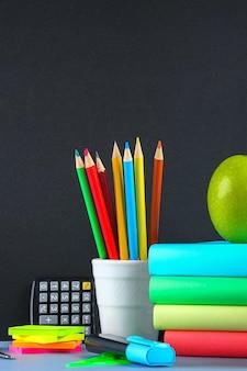 Una pila de libros y papelería en pizarra. mesa de trabajo, educación, escuela.