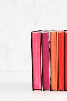 Pila de libros con la pila del color en la tabla blanca. copia espacio