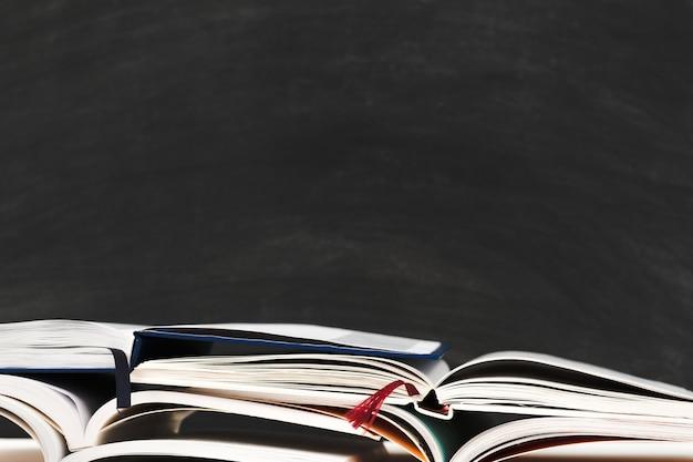 Pila de libros en la pizarra de la escuela con bolígrafos y lápices