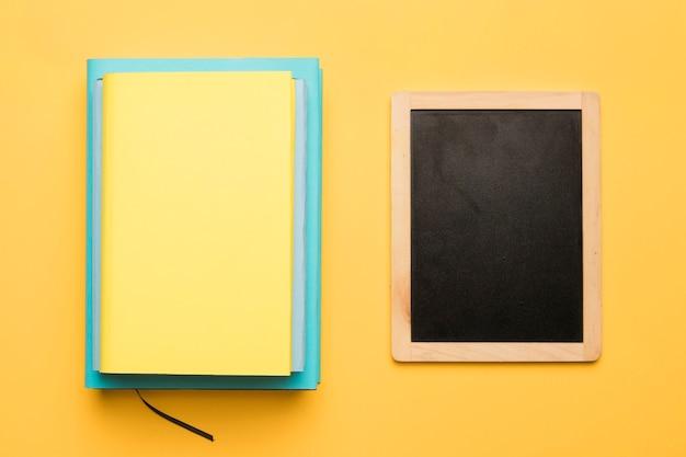Pila de libros y pizarra sobre fondo amarillo