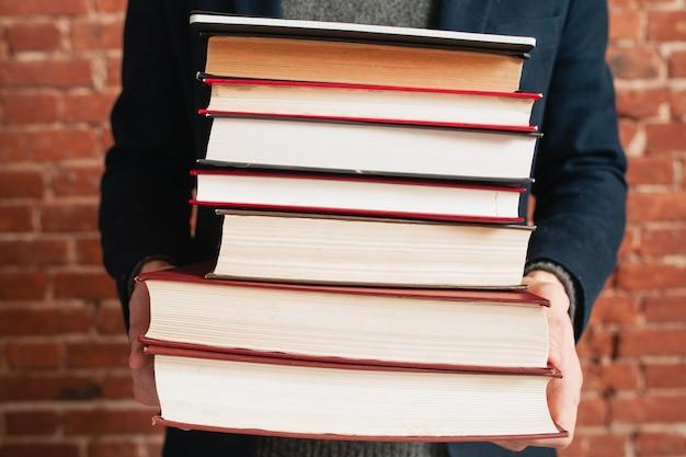 Pila de libros en primer plano de manos masculinas.