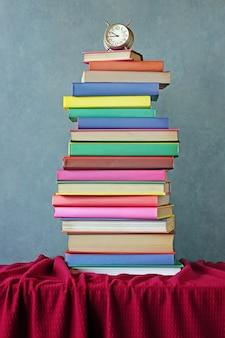 Pila de libros y reloj despertador en un paño rojo