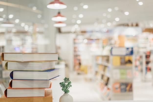 Pila de libros en la sala de la biblioteca y fondo de estantería borrosa