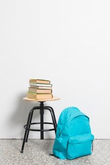 Pila de libros en silla de taburete con mochila azul en el piso