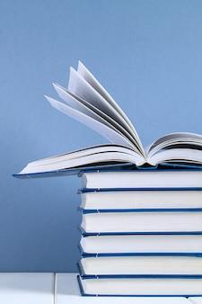 Una pila de libros sobre fondo azul. un libro escondido encima de la pila.