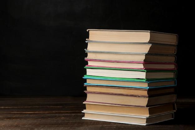 Una pila de libros sobre una mesa de madera marrón y sobre un fondo negro. libros viejos. educación. colegio. estudio con espacio para inscripciones