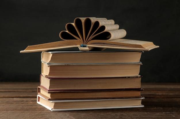 Una pila de libros sobre una mesa de madera marrón y sobre un fondo negro. libros viejos. educación. colegio. estudio