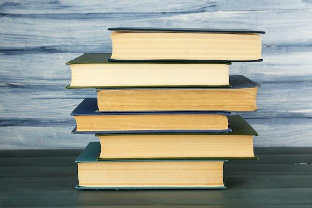 Pila de libros sobre la mesa de madera en la pared de madera azul