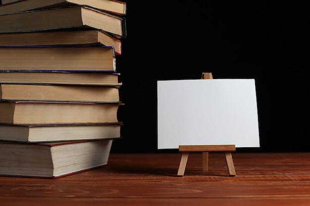 Una pila de libros sobre una mesa, un pequeño caballete con una tarjeta blanca en blanco o una hoja de papel
