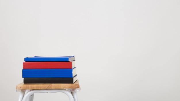 Una pila de libros sobre una silla. aisló un fondo blanco.