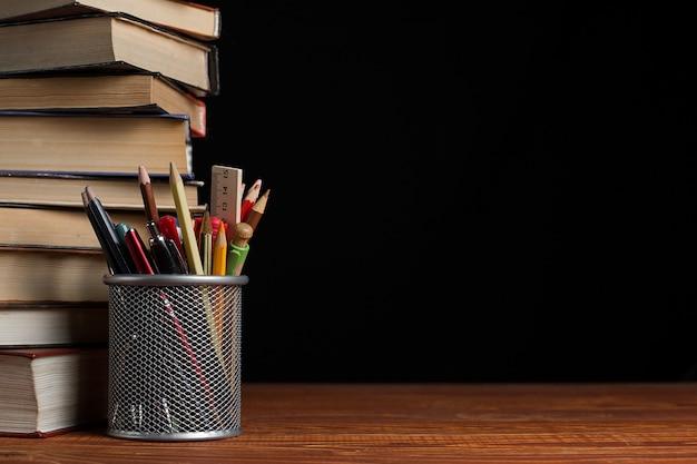 Una pila de libros y un soporte para bolígrafos sobre una mesa, sobre un fondo negro.