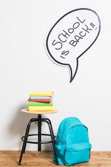 Pila de libros en taburete y mochila escolar hablando por bocadillo