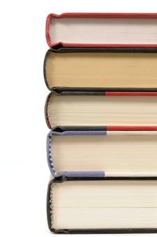 Pila de libros de tapa dura contra un fondo blanco