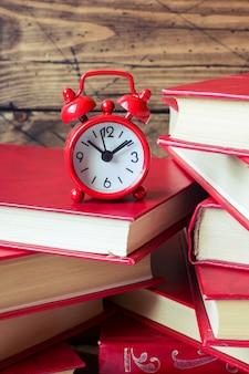 Una pila de libros de tapa dura y un reloj de alarma en una tabla de madera. copia espacio para texto