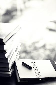 Una pila de libros de texto en el alféizar de la ventana y utensilios de escritura.