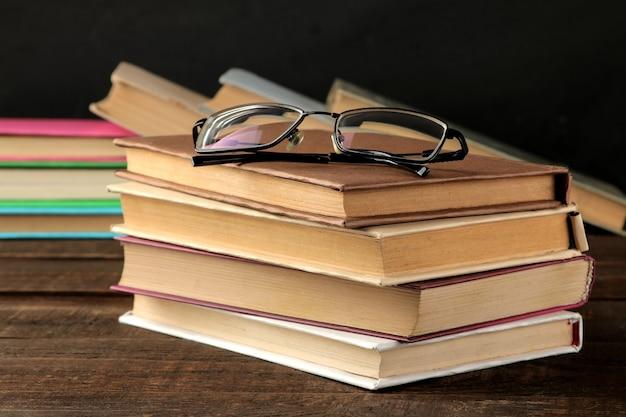 Una pila de libros y vasos sobre una mesa de madera marrón y sobre un fondo negro. libros viejos. educación. colegio. estudio