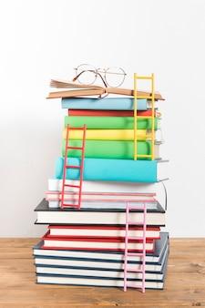 Pila de libros con vidrios y escaleras.