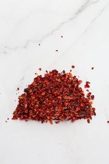 Pila machacada de la pimienta roja de la pimienta roja de la tapa en el fondo blanco. montón de hojuelas de pimiento rojo, ají rojo molido pimentón hojuelas de chile fresco y triturado. concepto de cocina, especias y cocina.