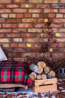Una pila de madera de abedul cerca del sofá con una manta roja en la terraza abierta de invierno