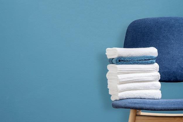 Pila de maquetas de toallas limpias en silla de madera con fondo de pared azul, espacio de copia.