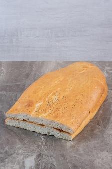 Pila de media hogaza de pan tandoori cuidadosamente rebanada sobre fondo de mármol. foto de alta calidad