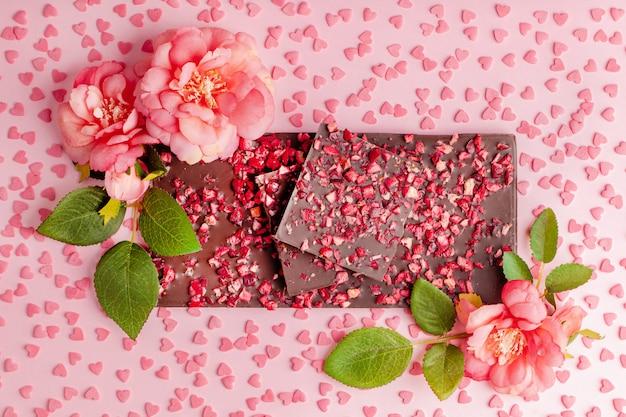 Pila de mentiras de chocolate con trozos de fresas secas en mesa rosa con flores