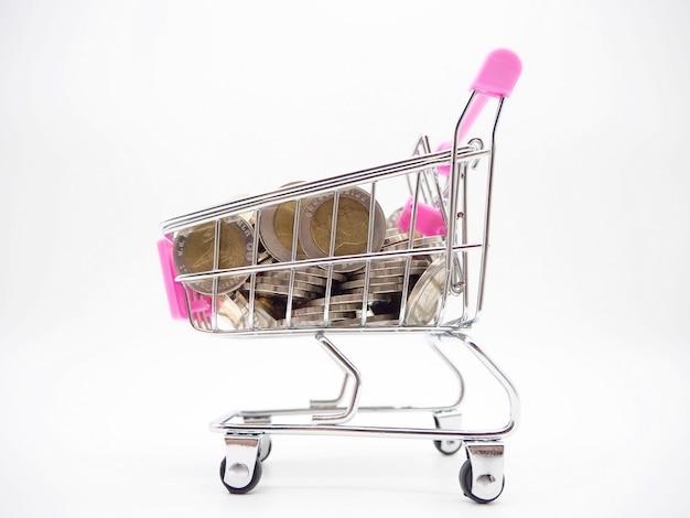 Pila de moneda en el carrito de compras sobre fondo blanco y gris