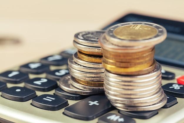 Pila de monedas y calculadora, concepto de finanzas empresariales