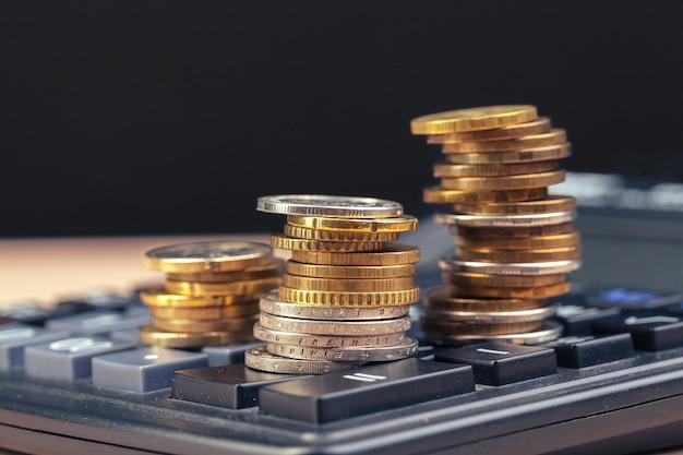 Pila de monedas y calculadora, idea conceptual para finanzas empresariales