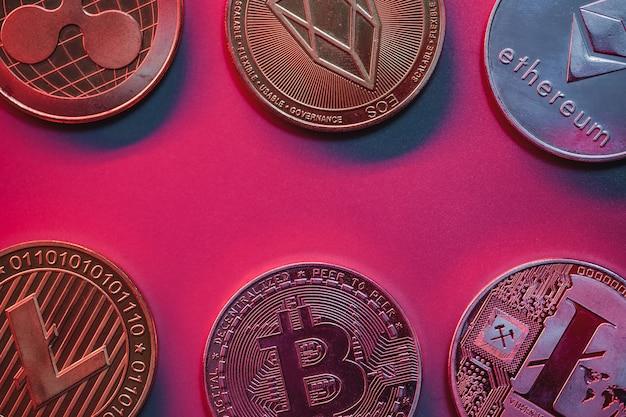 Pila de monedas criptográficas sobre fondo rojo, rosa con iluminación de neón. lugar para el texto.