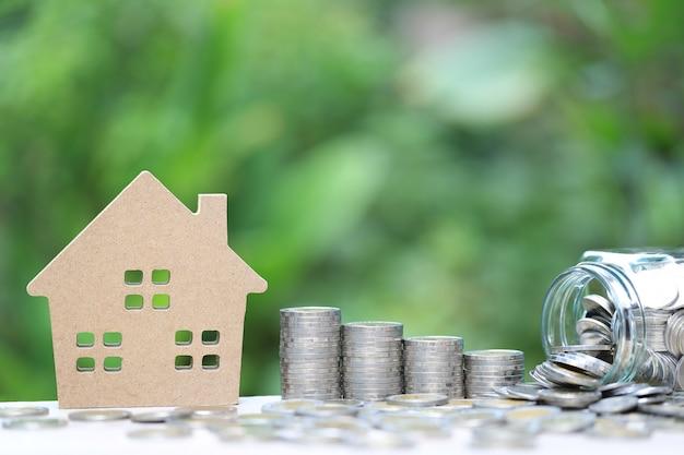 Pila de monedas de dinero y casa modelo sobre fondo verde natural