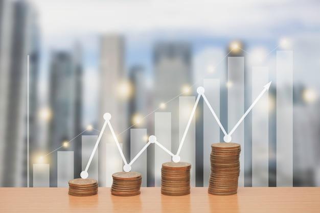 Pila de monedas de dinero en una mesa con creciente gráfico y flecha hacia arriba.