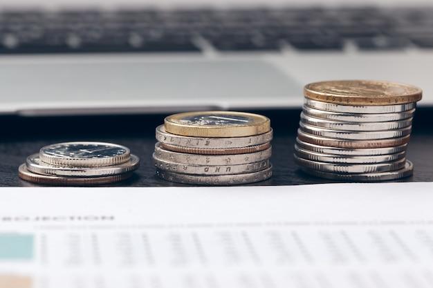 Pila de monedas de dinero con papel cuadriculado en mesa de madera