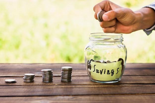 Pila de monedas y frasco con monedas de ahorro