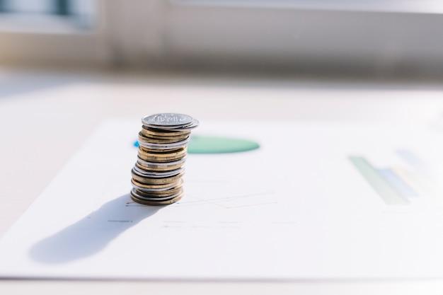 Pila de monedas en el gráfico sobre la mesa
