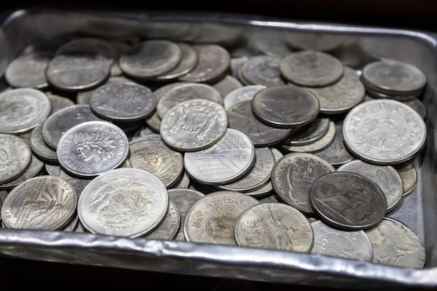 Pila de monedas de metal de diferentes denominaciones y diferentes países en caja de metal