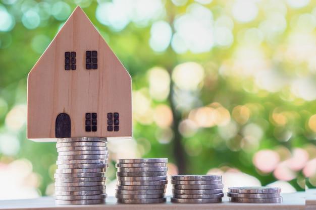 Pila de monedas y modelo de casa, planeando comprar casa nueva