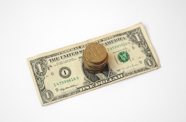 Pila de monedas en un papel de billete de ucrania hryvnia un dólar estadounidense