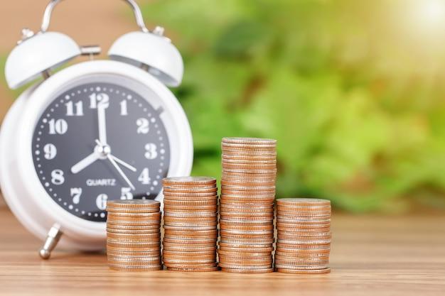 Pila de monedas con reloj para ahorrar dinero concepto