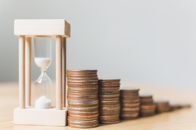 Pila de monedas con reloj de arena