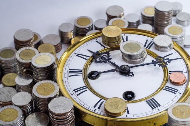Pila de monedas en el reloj vintage
