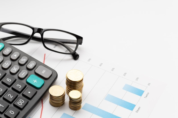 Pila de monedas sobre el gráfico con gafas